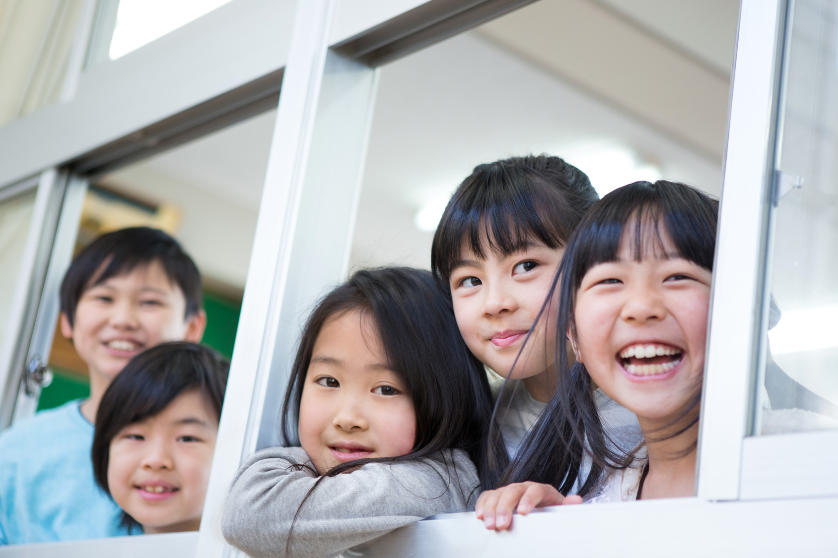 窓から顔を出す小学生